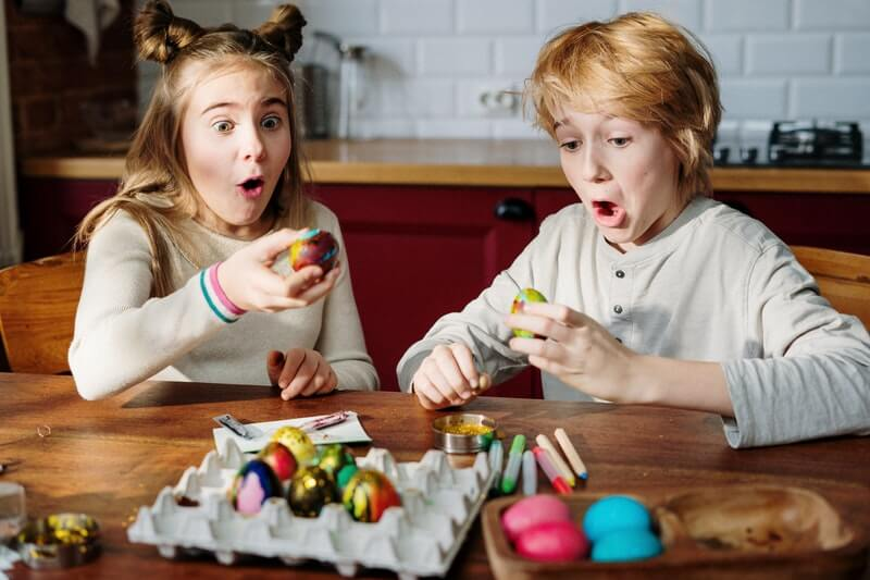 a boy and a girl dyeing Easter eggs